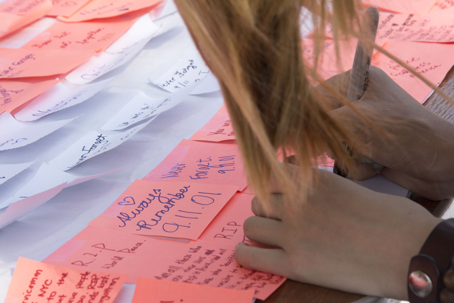 A large white sheet was plastered with the messages of passing students on white and salmon colored post-it notes.