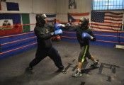 Royals Boxing Gym coach, Tom Cooper, spars with his star student, 13-year-old Jason Romero. Photo by  Jimin Kim (March 18, 2015).
